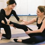 women in black top and black leggings stretching